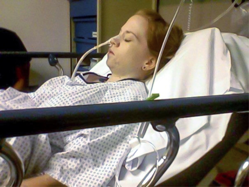 Laying on a hospital bed in ER with NG tube in