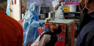 A healthcare worker wearing protective gear takes a swab sample from a man for a rapid antigen test outside a tea stall at a bus terminal in Ahmedabad, India, 15 July 2020 (Photo: Reuters/Amit Dave).