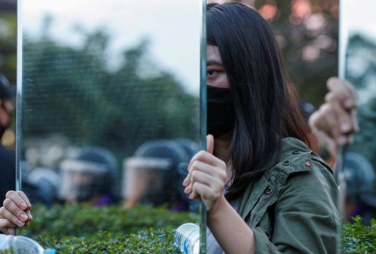Protesters hold mirrors in front of riot police officers during a pro-democracy rally demanding the prime minister to resign and reforms on the monarchy, at 11th Infantry Regiment, in Bangkok, Thailand, 29 November 2020 (Photo: Reuters/Soe Zeya Tun).