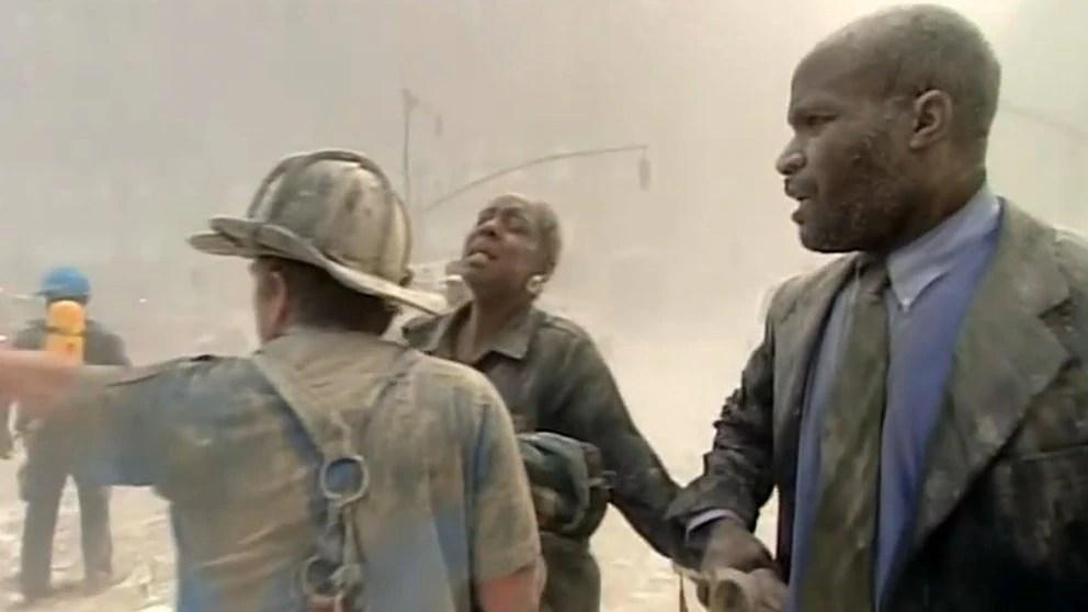 Neoyorquinos en estado de confusión en el escombro y bomberos guiándolos.