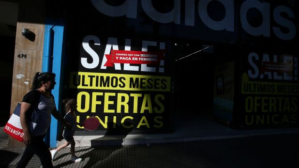 "People walk past a store with signs reading ""Unique offers, last months"" and ""Buy today and pay in February,"" in Buenos Aires, Argentina December 12, 2018. Picture taken December 12, 2018. REUTERS/Agustin Marcarian"
