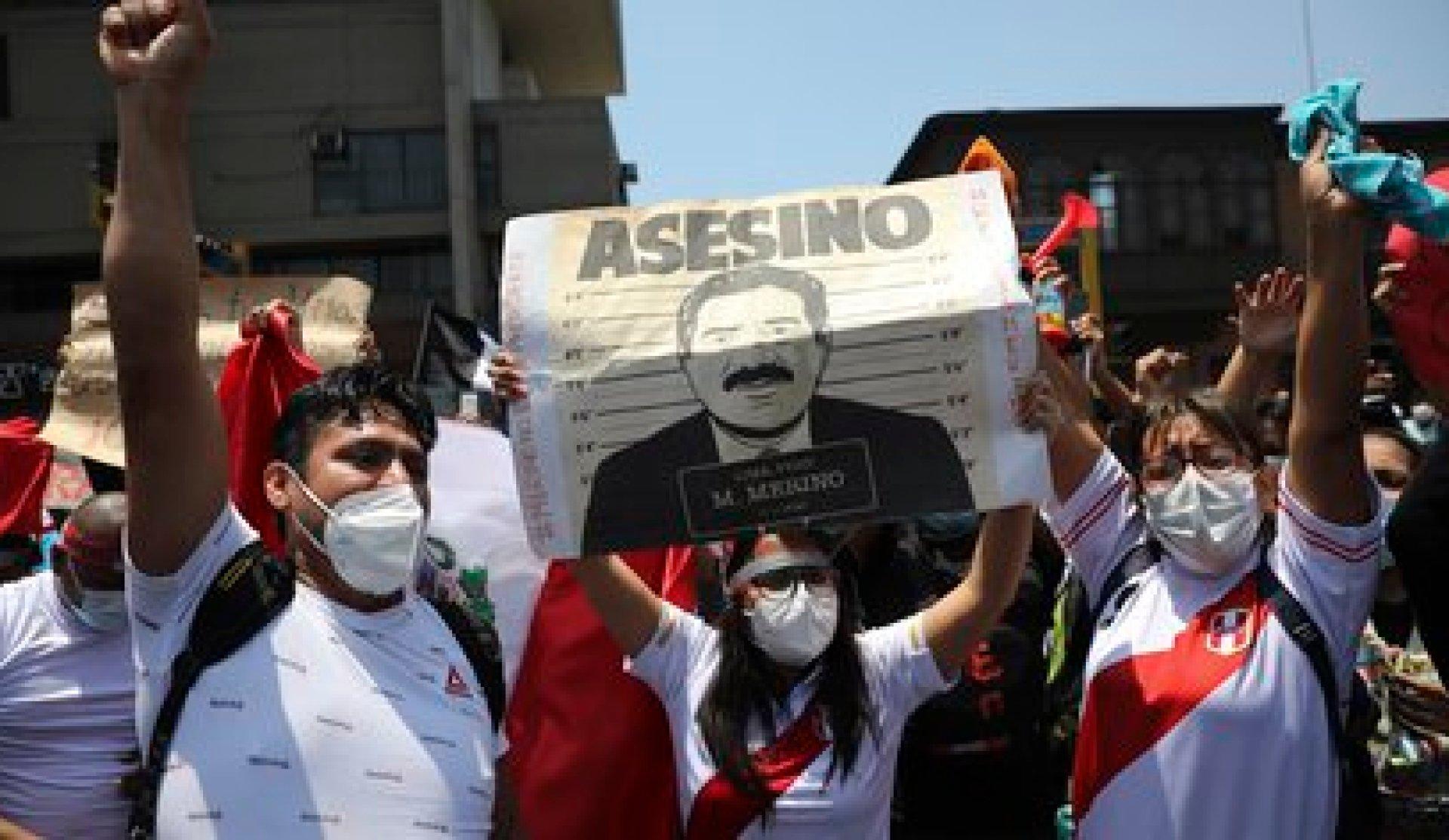 """Manifestantes pidiendo la renuncia del presidente interino, Manuel Merino, con un cartel que dice """"Asesino"""", poco antes de que Merino anunciara su renuncia en Lima, Perú, el domingo 15 de noviembre de 2020. (AP Foto/Rodrigo Abd)"""