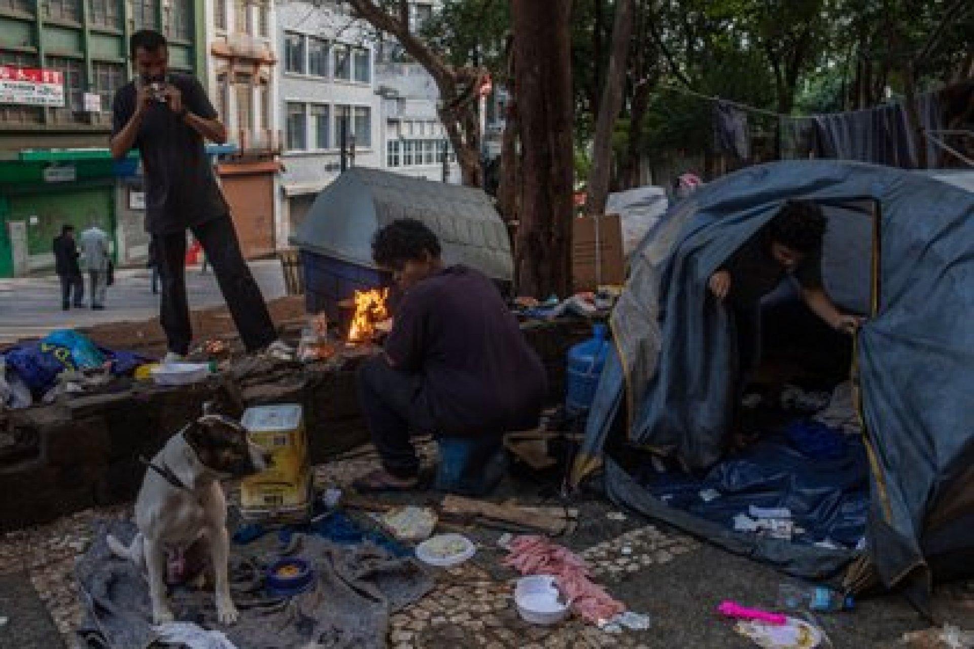 Daniela dos Santos prepara una comida en el centro de São Paulo. La pandemia agravó la crisis económica de Brasil y ha hecho aumentar las filas de los desempleados y las personas sin hogar. (Victor Moriyama / The New York Times)