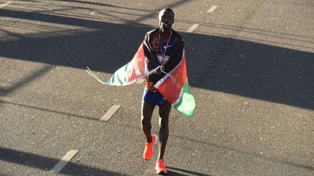El ganador de la carrera, envuelto en la bandera de su país natal