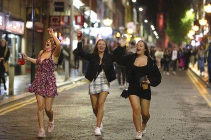Jóvenes disfrutan de la noche en el centro de Liverpool antes de que entren en vigor restricciones en los horarios de los bares debido al aumento de casos de coronavirus. (Peter Byrne/PA vía AP)