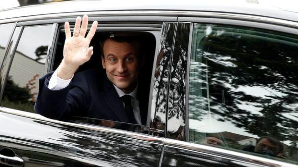 El candidato presidencial francés para el 'En Marche!' Emmanuel Macron saluda al salir de su casa para votar en la primera vuelta de las elecciones (EFE)