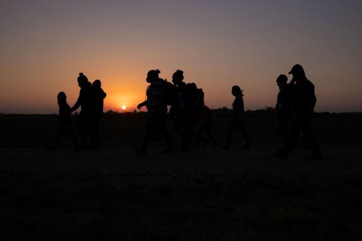 The sun rises as asylum-seeking migrants' families from Honduras and El Salvador walk towards the border wall after crossing the Rio Grande river into the United States from Mexico on a raft, in Penitas, Texas, U.S., March 26, 2021. REUTERS/Adrees Latif     TPX IMAGES OF THE DAY