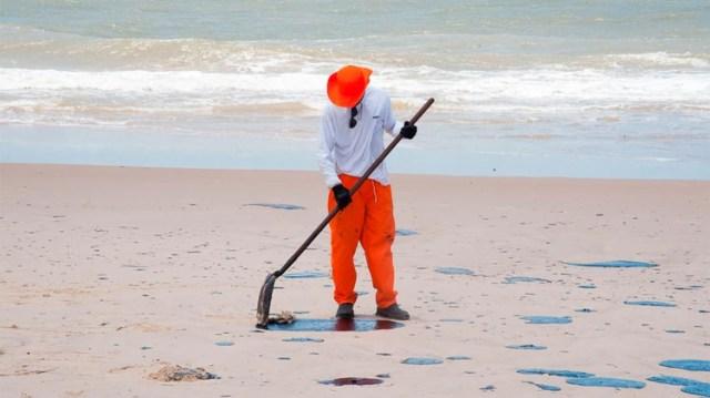 Una persona limpia las manchas de petróleo en una de las playas afectadas (AFP)