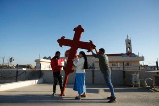 Cristianos iraquíes colocan una cruz en una iglesia en Qaraqosh, Irak, 22 de febrero de 2021. Los cristianos de Irak esperan que la visita del papa Francisco en marzo les ayude en su lucha por la supervivencia. (AP/Foto/Hadi Mizban)