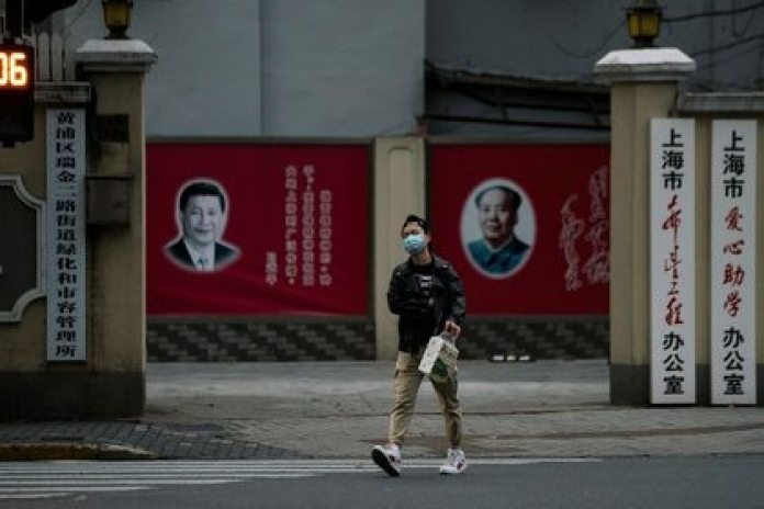 A man wearing a mask walks past portraits of Chinese President Xi Jinping and the late Chinese President Mao Zedong on a street in Shanghai, China.  February 10, 2020. REUTERS / Aly Song