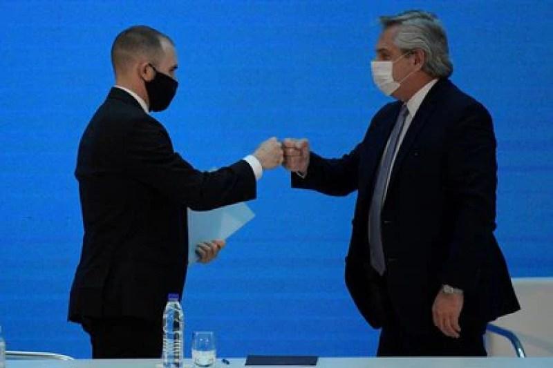 El presidente de Argentina, Alberto Fernández, saluda con choque de puños al ministro de Economía, Martín Guzmán (REUTERS)
