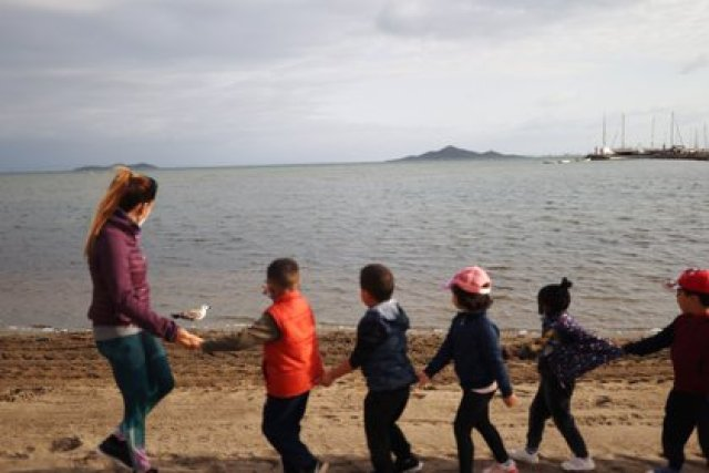 A teacher and her students from the Felix Rodriguez de la Fuente school look at a seagull during a class, as part of a project known as 'Aire Limpio' (Fresh Air) at the Playa de los Nietos (The Grandchildren's Beach), which aims to use better air quality for children during the coronavirus disease (COVID-19) pandemic, near Cartagena, southern Spain April 8, 2021. Picture taken April 8, 2021. REUTERS/Nacho Doce