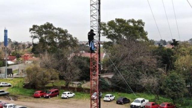El policía Oscar Pagano, trepado a una torre, que amenaza con lanzarse al vacío (Lihueel Althabe)