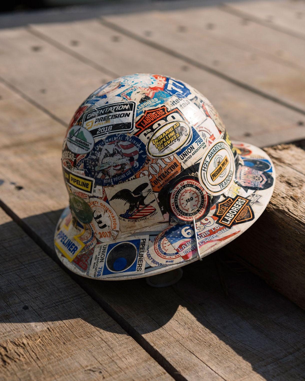 El casco del trabajador de la construcción Ever Guardado está cubierto con múltiples calcomanías para la mano de obra organizada y otras designaciones (Justin T. Gellerson / The New York Times)