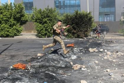 Un soldado del ejército libanés se abre paso a través de una barricada incendiada por manifestantes al norte de Beirut, el 12 de junio de 2020 (REUTERS/Aziz Taher)