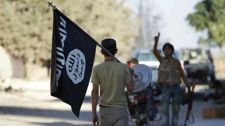 Un rebelde lleva como trofeo una bandera del Estado Islámico, durante la avanzada sobre Dabiq (Reuters)