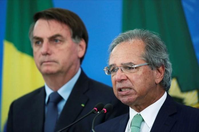 FOTO DE ARCHIVO. El ministro de Economía de Brasil, Paulo Guedes, habla junto al presidente, Jair Bolsonaro, durante un comunicado de prensa que anuncia medidas económicas, en medio del brote de la enfermedad por coronavirus (COVID-19), en Brasilia, Brasil. 1 de abril de 2020. REUTERS/Ueslei Marcelino