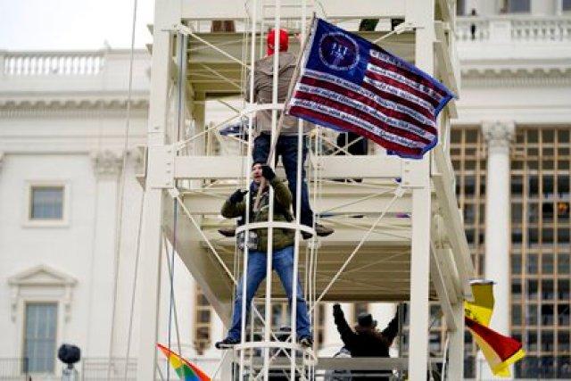 Partidarios de Trump escalaron estructuras metálicas frente al Capitolio este miércoles (AP Photo/Julio Cortez)