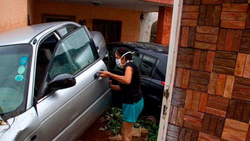 A woman checks a vehicle that was dragged and damaged by the rain in Maracaibo (EFE / Henry Chirinos)