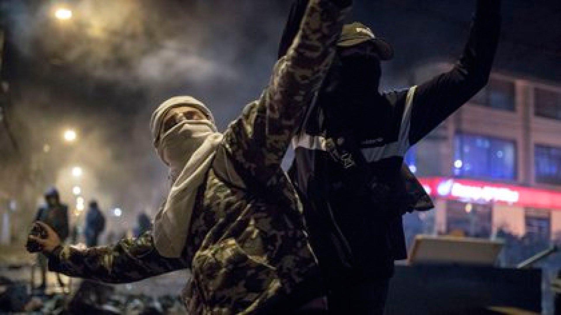 Un manifestante con la cara oculta lanza proyectiles a un cuerpo policial en Bogotá (AP Photo/Ivan Valencia)