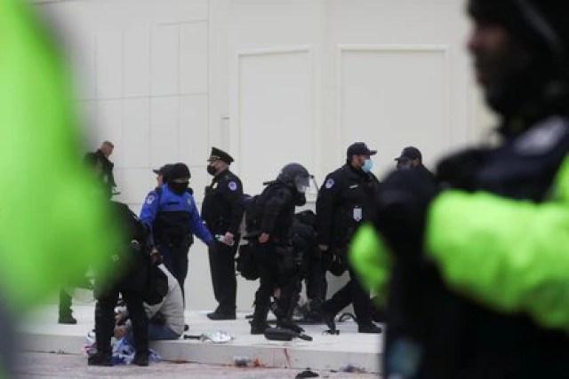 Oficiales de policía caminan alrededor del Capitolio después del choque con los partidarios de Trump. REUTERS/Leah Millis