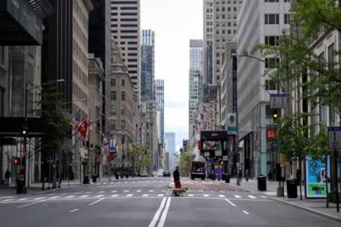 Мужчина гуляет с собаками по почти пустой 5-й авеню и закрывает роскошные магазины 11 мая 2020 года (REUTERS / Mike Segar)