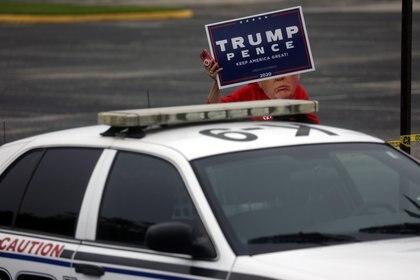 Un partidario del presidente Donald Trump con una máscara que representa a Trump sostiene una pancarta después de un evento de campaña de Joe Biden en las afueras del Hillsborough Community College en Tampa, Florida, Estados Unidos, el 15 de septiembre de 2020 (REUTERS/Leah Millis)