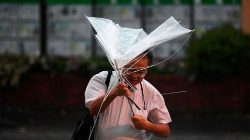 Un hombre con un paraguas cruza una calle temprano en la mañana bajo la lluvia. (Foto por Charly TRIBALLEAU / AFP)