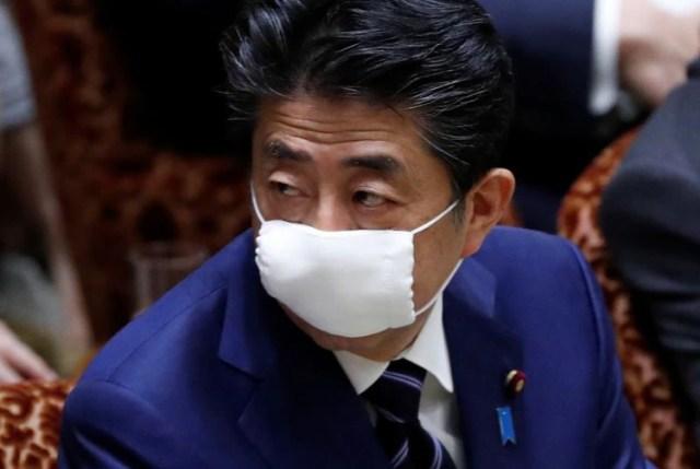 El primer ministro de Japón, Shinzo Abe, con la boca y nariz cubiertas con una mascarilla protectora durante una sesión parlamentaria de la Cámara Alta, tras el brote de coronavirus en Tokio, Japón, el 1 de abril de 2020. REUTERS/Issei Kato