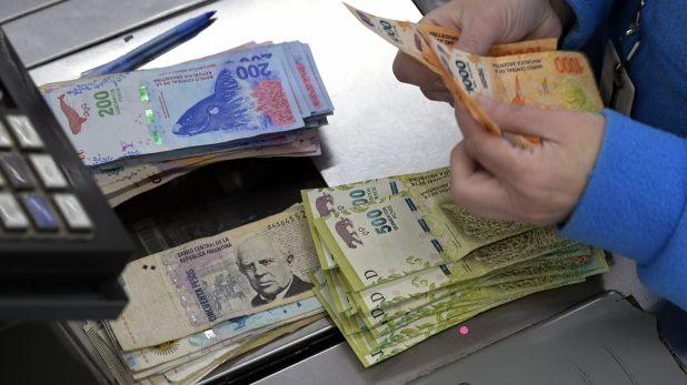 Muchos de quienes tienen capacidad de ahorro cambian sus pesos por dólares, como refugio de valor (Juan Mabromata, AFP)