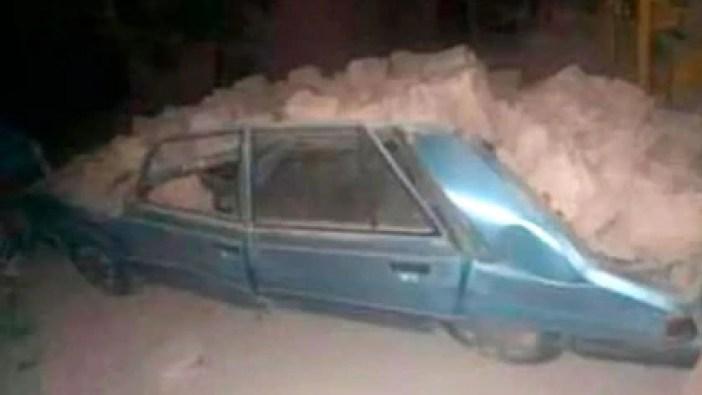 Un auto atrapado debajo de los escombros