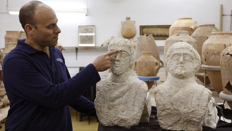 El arqueólogo israelí Eitan Klein muestra detalles de los bustos hallados, pertenecientes al período Romano