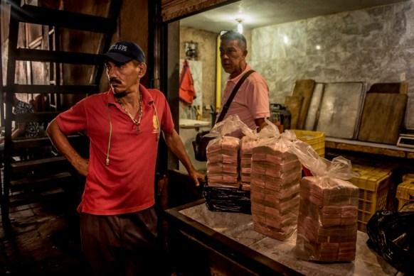 Bolsas de dinero, que han perdido buena parte de su valor, en un puesto mercado popular de alimentos en Maracaibo. (Meridith Kohut/The New York Times)