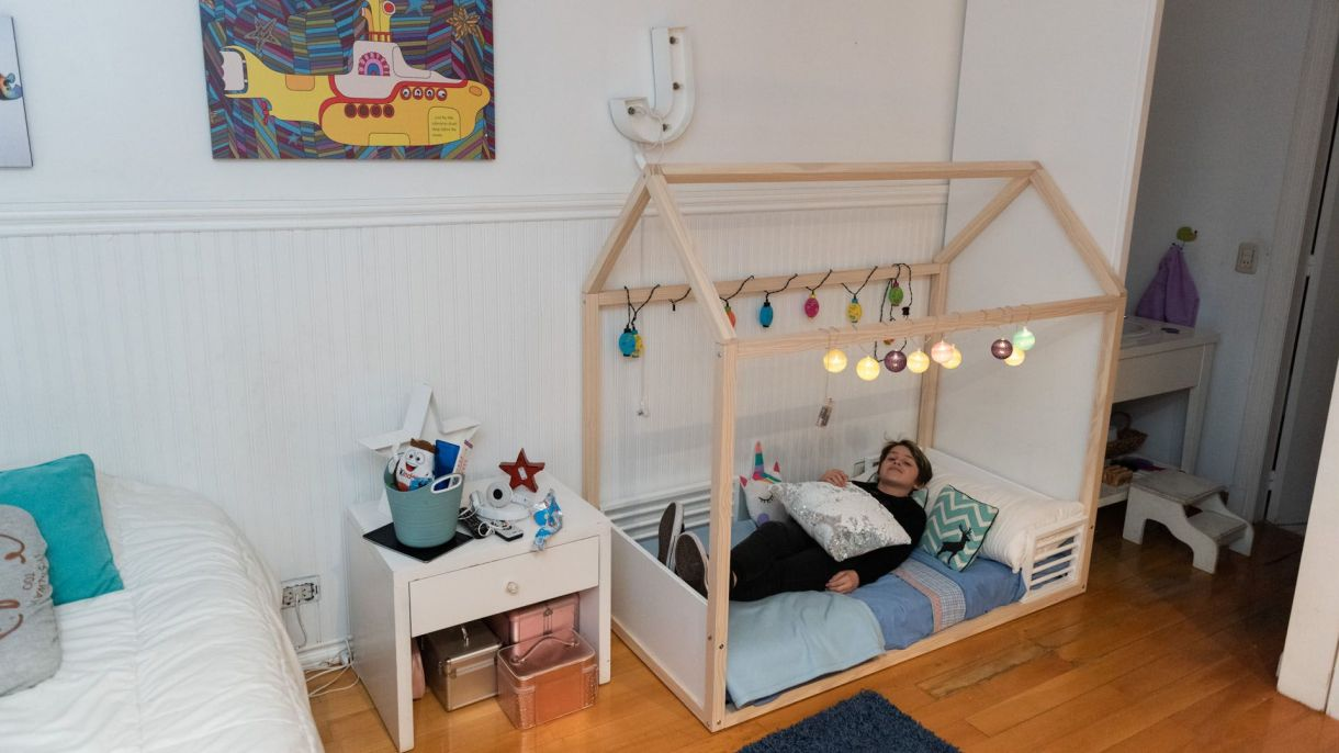 En su habitación, el niño tiene otra cama para cuando recibe la visita de sus amigos. De fondo, el banquito que tiene en el baño para verse al espejo