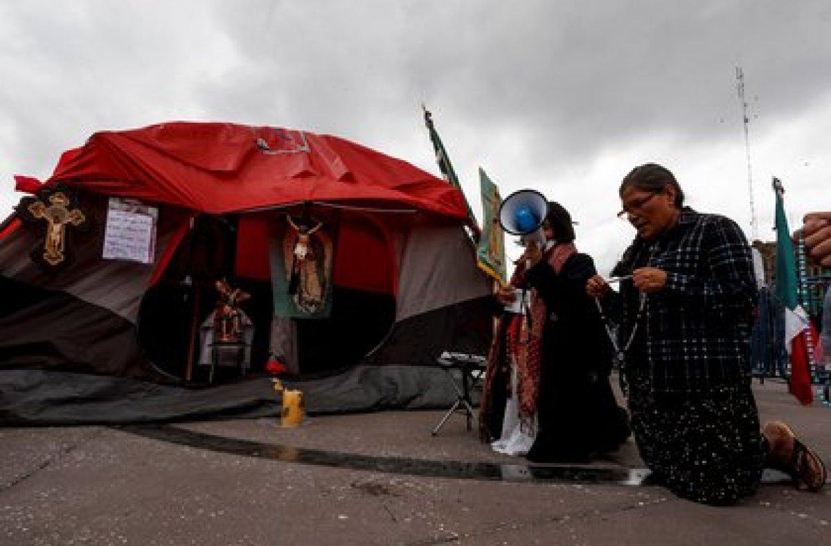 De rodillas, manifestantes de FRENAAA le piden a Dios que AMLO no siga como presidente (Foto: EFE)