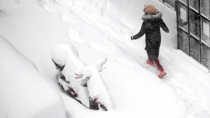 Una mujer pasa caminando entre la nieve, que cubrió una moto (AP Photo/Paul White)