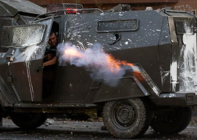Un carabinero dispara desde un blindado (AFP)