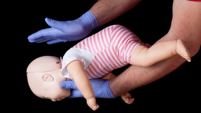 Si el paciente es menor de un año, debe ser colocado boca abajo en el antebrazo, sostenerle la cabeza y darle cinco palmadas con la base de la otra mano, entre los omóplatos (Shutterstock)