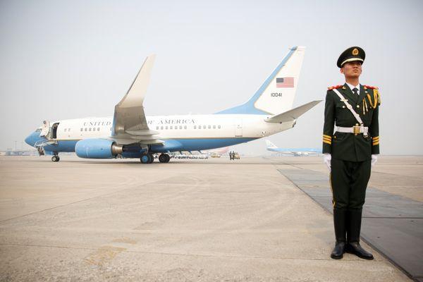 Un oficial de la policía china custodia la llegada del avión del gobierno estadounidense. (AFP)