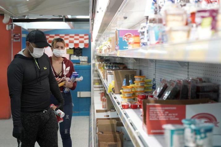 Foto de archivo. Personas que usan mascarillas seleccionan alimentos en un supermercado horas antes de la cuarentena obligatoria decretada por el gobierno colombiano como medida preventiva contra la propagación del coronavirus, en Bogotá, Colombia 24 de marzo, 2020. REUTERS/Nathalia Angarita.