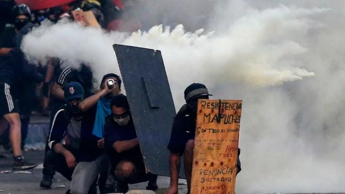 Manifestantes durante una represión a las protestas en Chile (Photo by JAVIER TORRES / AFP)
