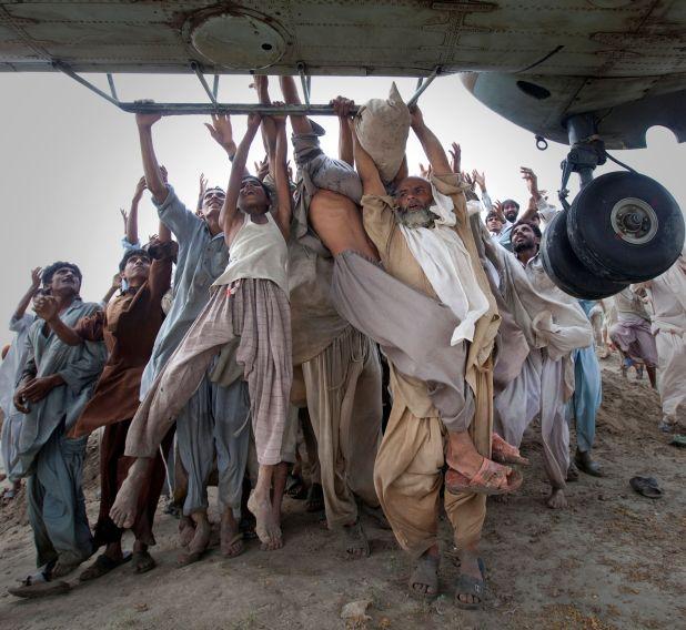 Víctimas de la inundación que buscaban escapar, agarran las barras laterales de un helicóptero del Ejército que volaba y llegaba para distribuir alimentos en el distrito de Muzaffargarh, provincia de Punjab, Pakistán, el 7 de agosto de 2010 (REUTERS/Adrees Latif)