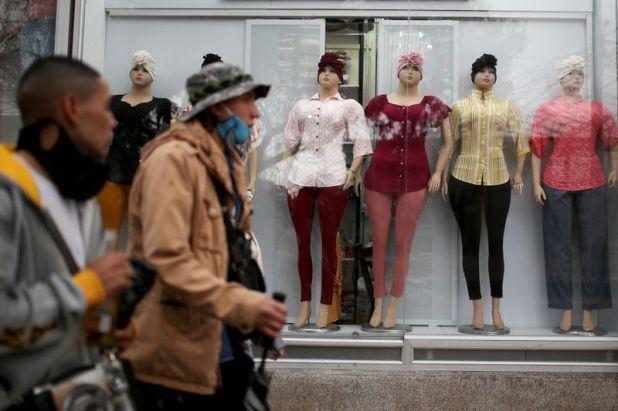 Imagen de archivo de personas caminando frente a una tienda de ropa femenina, en medio del brote de coronavirus, en Bogotá, Colombia, Junio 17, 2020. REUTERS/Luisa Gonzalez
