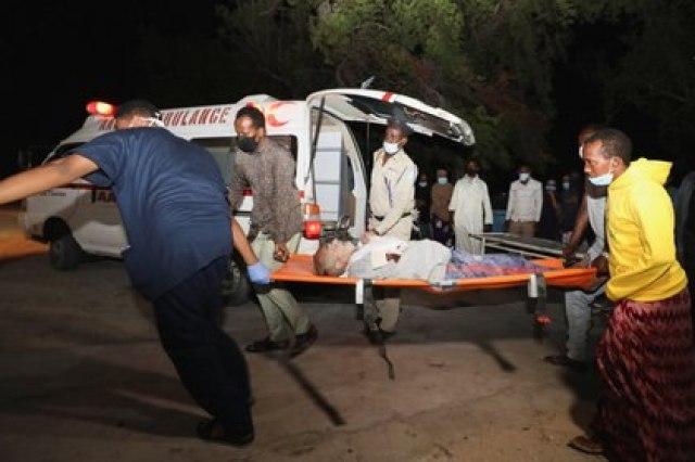 Unas personas asisten a un herido en el exterior del hospital Madina tras la explosión en el restaurante cerca del puerto en Mogadiscio, Somalia, el 5 de marzo de 2021. REUTERS/Feisal Omar
