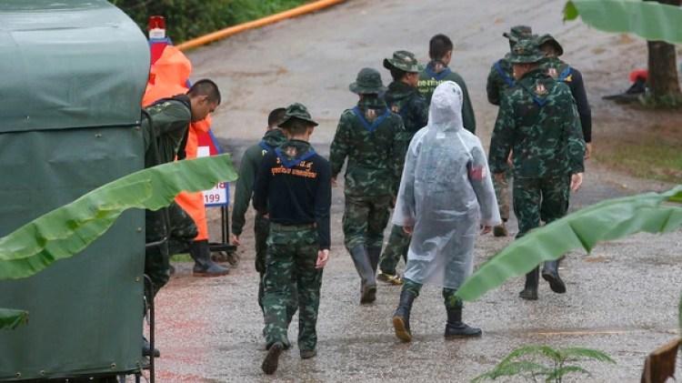 Personal socorrista en las afueras de la cueva y bajo las lluvias traídas por el Monzón (AP)