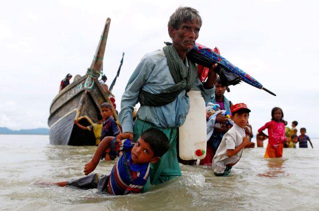 Un hombre refugiado rohingya tira de un niño mientras caminan hacia la orilla después de cruzar la frontera entre Bangladesh y Myanmar en barco a través de la Bahía de Bengala en Shah Porir Dwip, Bangladesh, 10 de septiembre de 2017.