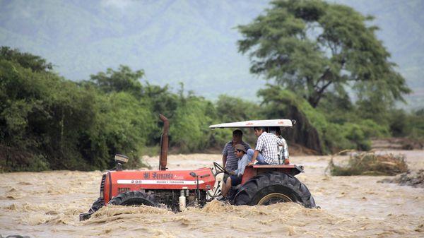 Ciudadanos a las afueras de Chiclayo (700 kilómetros al norte de Lima) usan un tractor para desplazarse entre las inundaciones (AFP)