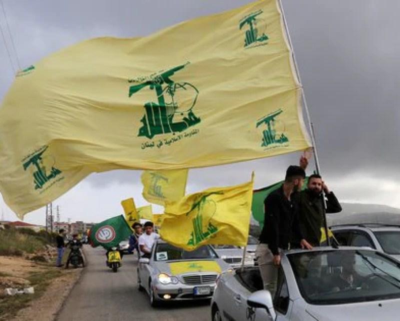 Un convoy de vehículos ondea banderas de Hezbollah. Foto: REUTERS/Aziz Taher