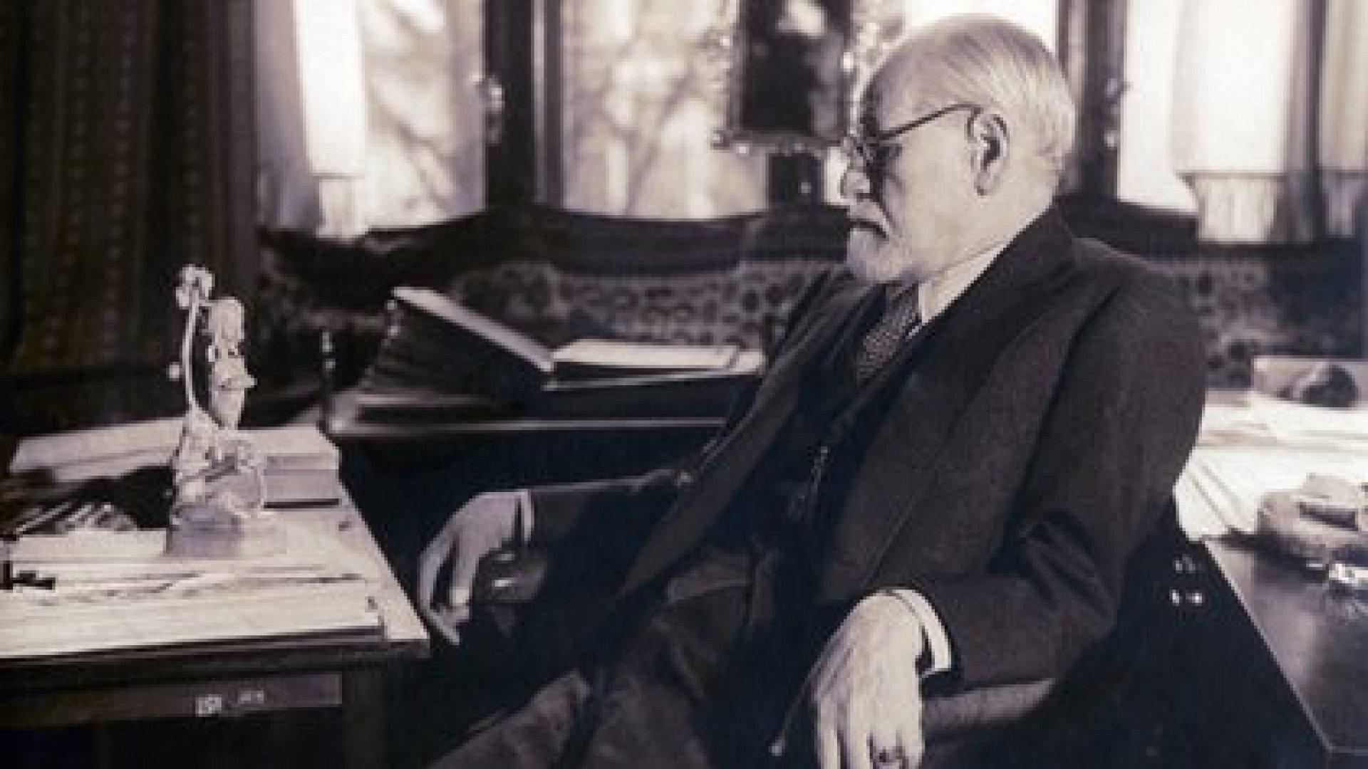 Sigmund Freud sentado en su estudio contemplando una figura tallada en su escritorio. 1937. Fotografía tomada por la Princesa Marie Bonaparte (Everett/Shutterstock)