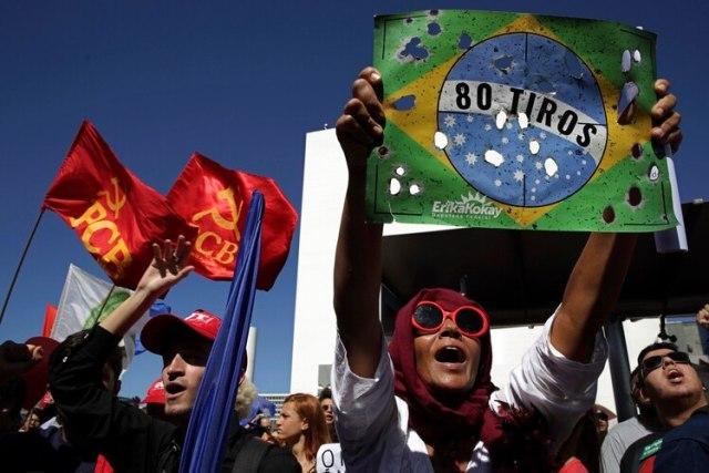 Un manifestante sostiene un cartel con la bandera brasileña y hoyos que simulan balazos en referencia a los soldados que dispararon el mes pasado contra un automóvil en el que viajaba una familia durante una protesta contra recortes a la educación en Brasilia, Brasil, el jueves 30 de mayo de 2019. (AP Foto/Eraldo Peres)